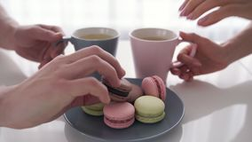 Close up of male and female hands holding cups of coffee with macaroons are on table. Close up of male and female hands holding cups of coffee. Couple is sitting stock video
