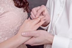Close-up male and female hands while putting a ring on a finger concept of marriage proposal Stock Image