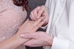 Close-up male and female hands while putting a ring on a finger concept of marriage proposal Stock Photo