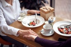 Close up male and female holding hands in cafe stock images