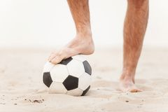 Close-up of male foot playing football on sand. Royalty Free Stock Image