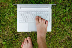 Close-up of male foot typing on laptop. Stock Images
