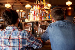 Close up of male friends at bar counter in pub. People, leisure and friendship concept - close up of male friends at bar counter in pub Royalty Free Stock Images