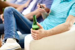 Close up of male friends drinking beer at home Stock Image