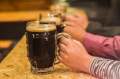 Close up of a male friends holding a craft beer in pub stock photos