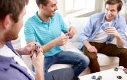 Close up of male friends playing cards at home Stock Images