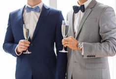 Close up of male gay couple with champagne glasses. People, celebration, homosexuality, same-sex marriage and love concept - close up of happy married male gay Royalty Free Stock Images