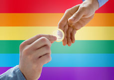 Close up of male gay couple hands giving condom. People, homosexuality, safe sex, sexual education and charity concept - close up of happy male gay couple hands Royalty Free Stock Photography
