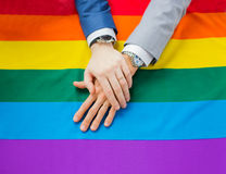Close up of male gay couple hands on rainbow flag Stock Photography
