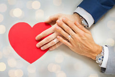 Close up of male gay couple hands with red heart Royalty Free Stock Image