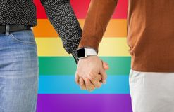 Close up of male gay couple hands with smartwatch. Same-sex relationships, lgbt and technology concept - close up of male gay couple holding hands with Stock Images