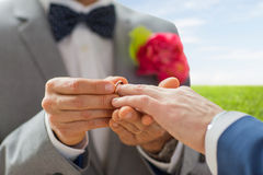 Close up of male gay couple hands and wedding ring. People, homosexuality, same-sex marriage and love concept - close up of happy male gay couple hands putting royalty free stock photography