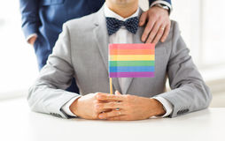 Close up of male gay couple holding rainbow flag. People, homosexuality, same-sex marriage and love concept - close up of happy male gay couple in suits and bow Stock Image