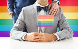 Close up of male gay couple holding rainbow flag. People, homosexuality, same-sex marriage and love concept - close up of happy male gay couple in suits and bow Royalty Free Stock Photo