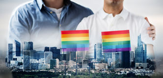 Close up of male gay couple holding rainbow flags Stock Photos