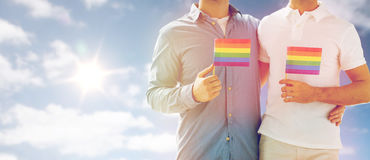 Close up of male gay couple holding rainbow flags. People, homosexuality, same-sex marriage and love concept - close up of happy male gay couple hugging and Royalty Free Stock Image