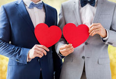 Close up of male gay couple holding red hearts. People, homosexuality, same-sex marriage, valentines day and love concept - close up of happy married male gay Stock Photo