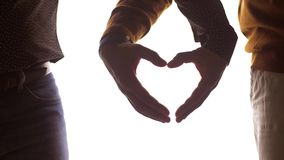 Close up of male gay couple making hand heart
