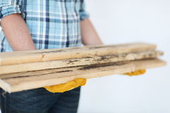 Close up of male in gloves carrying wooden boards Royalty Free Stock Photos