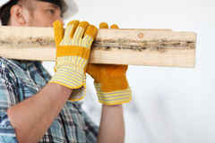Close up of male in gloves carrying wooden boards Stock Photos