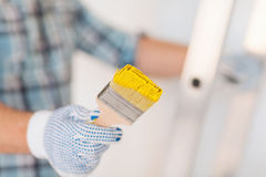 Close up of male in gloves holding paintbrush Royalty Free Stock Image