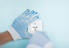 Close up of male in gloves installing new socket. Repair, building, electricity and home concept - close up of male in gloves installing new socket Royalty Free Stock Image
