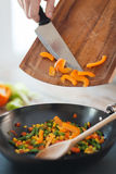 Close up of male hand adding peppers to wok Royalty Free Stock Images