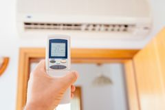 Close up on male hand adjusting home air condition Stock Photography