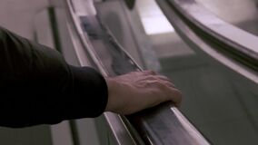 A close-up of a male hand on black rubber handrail of an escalator while moving down.