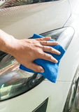 Close up male hand. With blue microfiber cloth cleaning the car Stock Photos