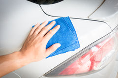 Close up male hand. With blue microfiber cloth cleaning the car Royalty Free Stock Image