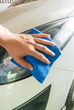 Close up male hand. With blue microfiber cloth cleaning the car Royalty Free Stock Images