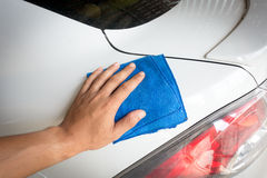 Close up male hand. With blue microfiber cloth cleaning the car Stock Photo