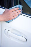 Close up of male hand cleaning car with microfiber cloth. Close up of male hand cleaning white car with microfiber cloth Royalty Free Stock Images