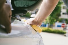 Close up of male hand cleaning car with sponge. Young adult cleaning front of his silver car by sponge at car wash Stock Images
