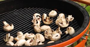 Close-up male hand cooking tasty barbeque mushrooms high angle stock video