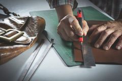 Close-up of male hand cutting with a knife to leather for bag. Royalty Free Stock Photography