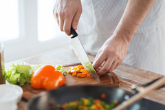 Close up of male hand cutting pepper on board Royalty Free Stock Photography