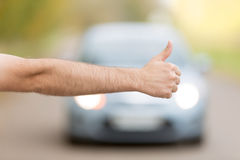 Close up of male hand hitchhiking. Asking a coming car for a ride on summer street Stock Photos