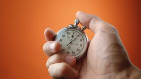 Male hand holding analogue stopwatch on orange color background. Time start with old chronometer man presses start