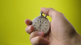 Male hand holding analogue stopwatch on yellow background. Time start with old chronometer man presses start button in