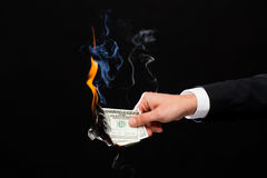 Close up of male hand holding burning dollar money Stock Images