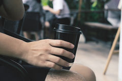 Close-up of male hand holding coffee to take away, vintage tone. Close-up of male hand holding coffee to take away cup with vintage tone Royalty Free Stock Image