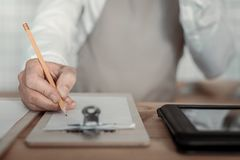 Close up of male hand that holding pencil. Working process. Competent waiter wearing uniform and making notes Royalty Free Stock Photo