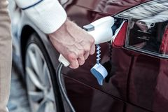 Close up of a male hand holding a petrol nozzle royalty free stock photography