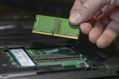 Close-up of a male hand holding a RAM card on the background of a disassembled laptop. stock photography