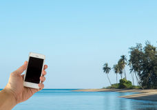 Close up of Male Hand Holding Smart Mobile Phone with Blank Screen on The Beach with Clear Sky used as Template Stock Images