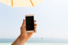 Close up of male hand holding smartphone on beach. Technology, travel, tourism, communication and people concept - close up of male hand holding smartphone with Stock Photography