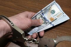 Close-up of a male hand holding a stack of US dollars with handcuffs on a brown background. The concept of violation of the law in stock photography