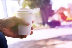 Close up of male hand holding take away coffee cup at morning ti stock photo